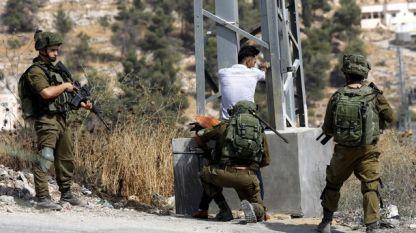Израелски войници претърсват палестинец на пропускателен пункт на Западния бряг