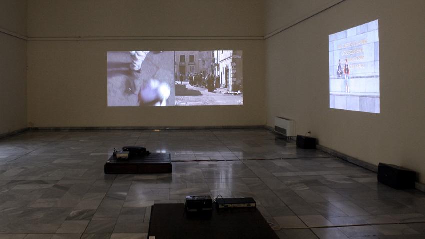 """Изглед от изложбата """"Между миналото което е на път да се случи и бъдещето което вече е било"""". В дъното: Един филм, 2004, двуканална видео инсталация; вдясно: Мону-ментално, 2011, видео"""
