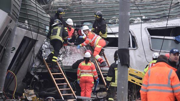 Спасители вадят хора от дерайлирали вагони.