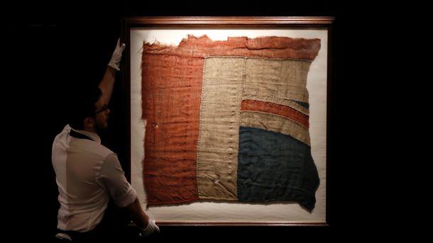 """Служител на аукционната къща """"Сотбис"""" позира с фрагмента от флага на кораба """"Виктъри"""", под който британския адмирал Нелсън печели битката при Трафалгар през 1805 г."""