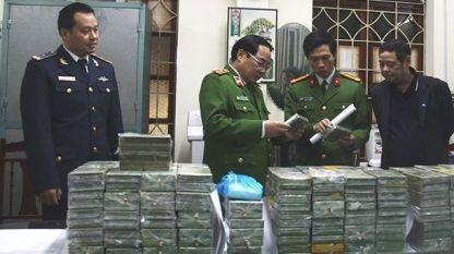 Виетнамски служители на реда до заловените почти 100 кг хероин.