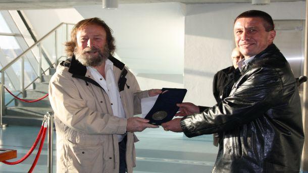 Победителят получава наградата си от директора на пристанището (вдясно)