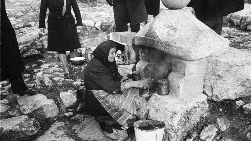 Granny Elena making coffee by the road, 1940