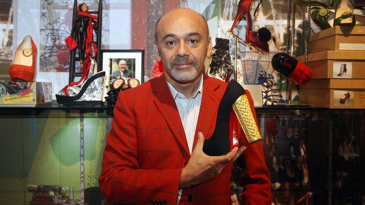 Кристиан Лубутен позира с една от своите обувки на изложба в Лондон през 2012 г. за 20-годишнината от създаване на своята марка, характерна с червените си подметки.