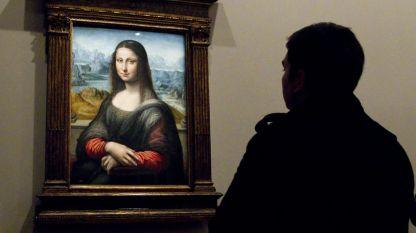 Посетител разглежда копие на Мона Лиза на Леонардо да Винчи на изложба в Лувъра, Париж.