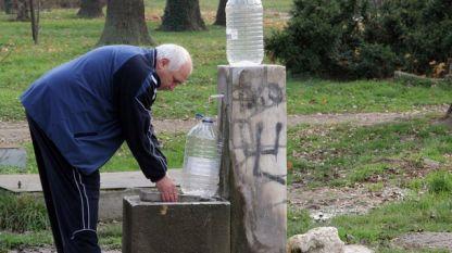 Жител на Хасково налива вода от чешмата в Градската градина.