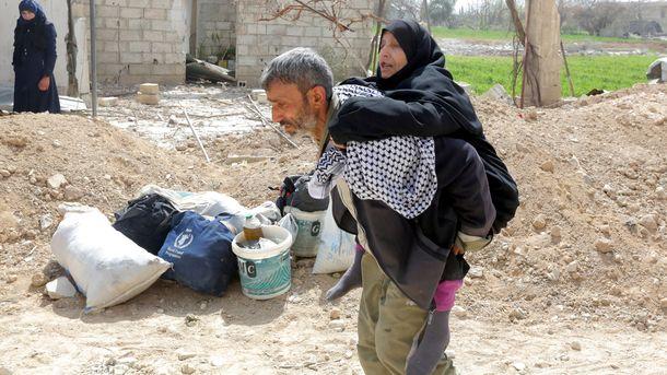 Сириец носи майка си при евакуацията от Източна Гута.