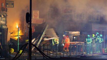Служители на спешни служби на мястото на експлозията и последвалия пожар късно в неделя в сграда в Лестър, Англия.