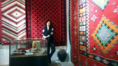 """""""Каракачка"""", един от най-старите модели чипровски килими (каракачка значи """"черноочка булка""""). Михайлина Павлова в залата с килимите в Историческия музей в Чипровци."""