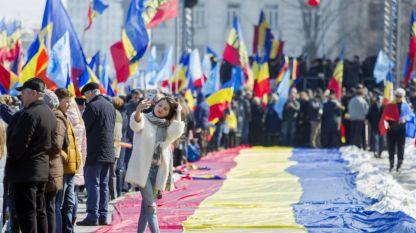 Момиче си прави селфи на фона на огромно румънско знаме по време на манифестация на централния площад в столицата на Молдова – Кишинев
