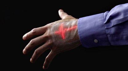 Тънкият и гъвкав дисплей върху ръката може да показва електрокардиограма, записана от малък сензор върху кожата.