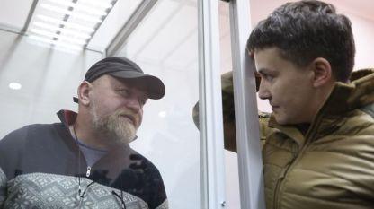 Депутатката Надежда Савченко (вдясно) разговаря с Володимир Рубан, който е поставен в клетка в съд в Киев на изслушването по обвиненията срещу него в заговор за убийство на висши представители на Украйна.