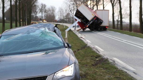 Обърнато ремарке и повредена кола в резултат на силните ветрове в Холандия.