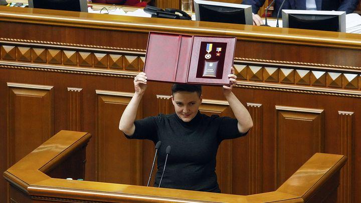 Надежда Савченко показва в парламента в Киев държавното си отличие на Герой на Украйна, преди да бъде лишена от депутатски имунитет.