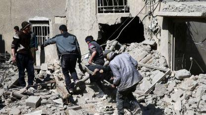 Хора изнасят тяло от руини в град Хамурия в Източна Гута, недалеч от Дамаск.
