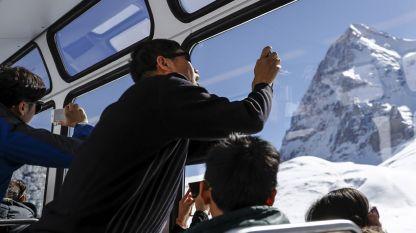 Туристи правят снимки, возейки се в зъбчатата железница Юнгфраубан в Швейцария.