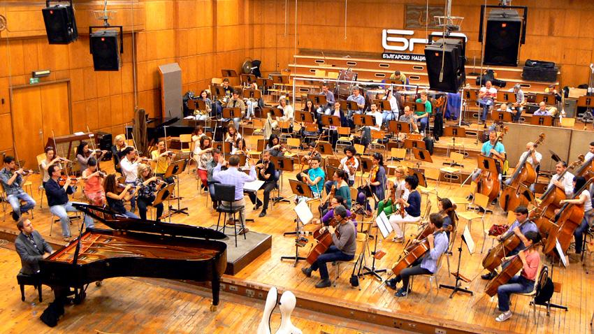 Момент от репетицията на Симфоничния оркестър на БНР с диригент Марк Кадин в Първо студио. На пианото – Алексей Чернов