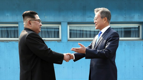Лидерите на Северна и Южна Корея се поздравяват на демаркационната линия в демилитаризираната зона между двете държави.