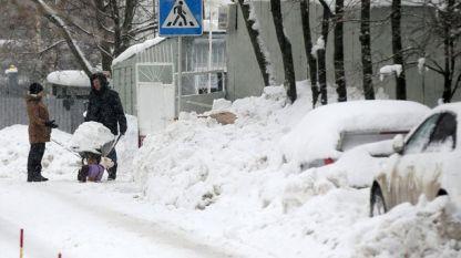 Жители на Москва разчистват покритите със сняг улици.