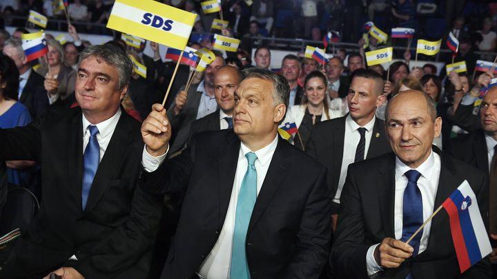 Унгарският премиер Виктор Орбан (в средата) вее партийния флаг  на Словенската демократична партия на Янез Янша (вдясно), която е фаворит да спечели изборите през юни.