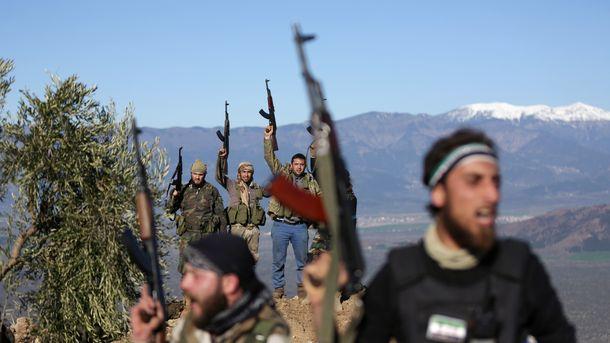 Подкрепяни от Турция бойци от Сирийската свободна армия размахват оръжия край град Африн в понеделник.