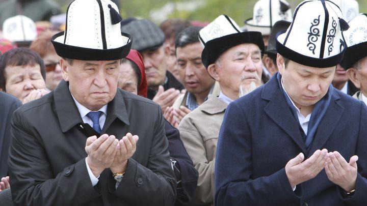 Президентът Сооронбай Жеенбеков (вляво) и премиерът Сапар Исаков се молят на възпоменателна церемония, отбелязваща 8-ата годишнина от гражданските безредици в Киргизстан на 7 април. Почти две седмици по-късно държавният глава изпрати правителството в оставка.