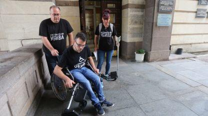 """Облечени в черните тениски """"Системата ни УБИВА"""", Емил Мавродиев, баща на 18-годишния Петър, успя да качи инвалидната количка на сина си по стълбите до приемната на Министерски съвет. На помощ дойдоха и други представители на протестиращите родители на деца с увреждания."""
