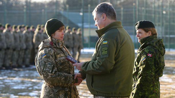 Украинският президент Петро Порошенко награждава военнослужеща пред погледа на генерал-губернатора на Канада Жюли Пайет (вдясно) при визитата им в четвъртък в Яворовския полигон в Лвовска област.