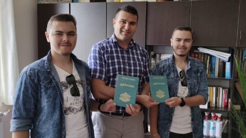 Ahmed Bozov 2021 yılı mezunlarından iki öğrenciye diplomarını takdim ederken.