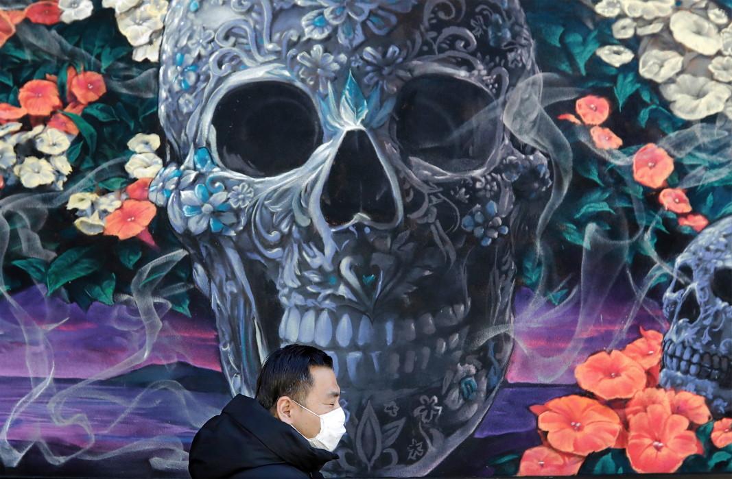 Пешеходещ със защитна маска, минаващ покрай уливен графит в Ню Йорк.