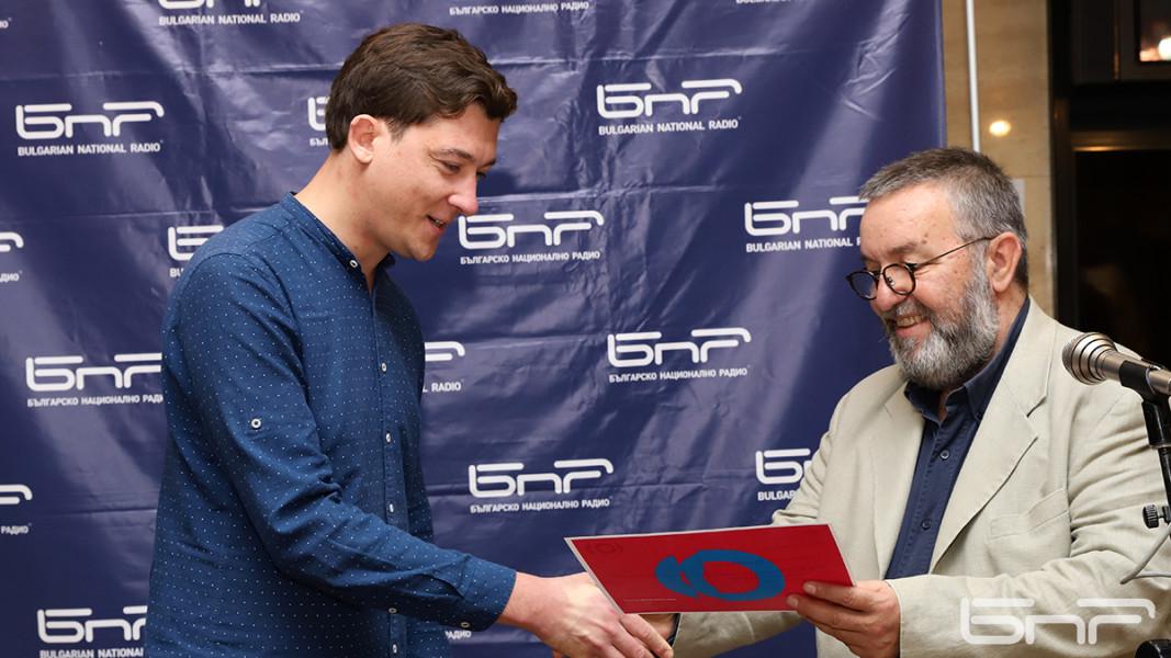 """Репортерът от програма """"Хоризонт"""" Добромир Цветков - отличник на тазгодишния випуск, получава дипломата си от и.д. генерален директор на БНР Антон Митов."""