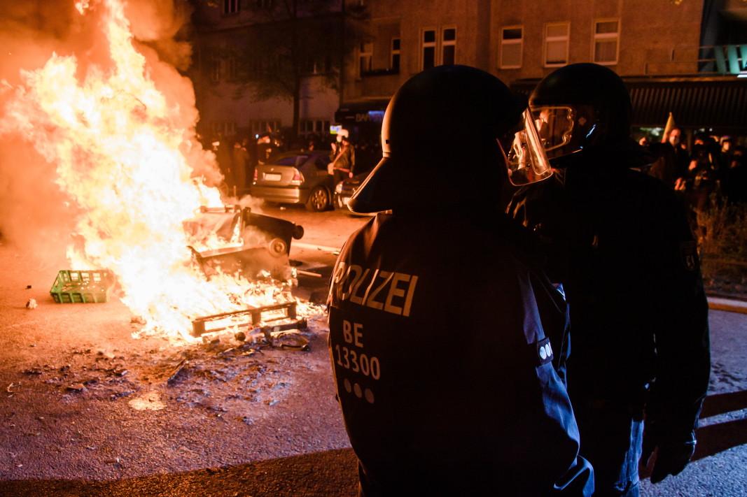 Полицейска част  за борба с безредиците заема позиция до горяща барикада по време на протест на 1 май в Берлин.