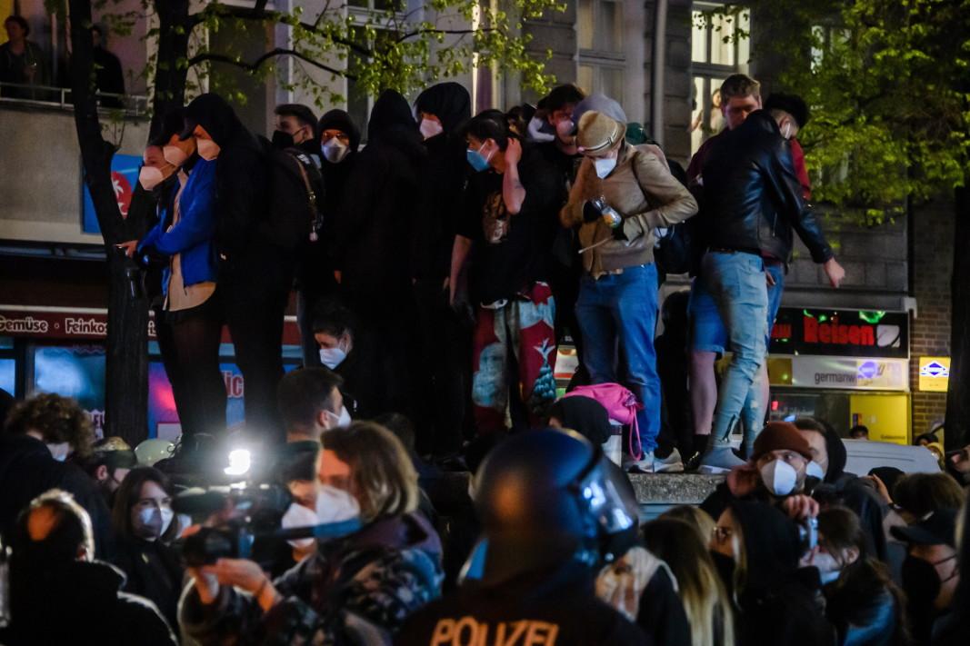Берлин - 1 май, 2021 г. Повечето от демонстрациите преминаха мирно. Настроението обаче се промени по-късно вечерта, след като полицията измъкна от тълпата крайно леви протестиращи, защото не се придържат към Covid разпоредби като социално дистанциране. Заедно с хиляди други, те участваха в шествие в демонстрацията Революционен първи май в знак на протест срещу расизма, капитализма и нарастващите наеми в града. Последваха тежки сбивания, протестиращи хвърляха стъклени бутилки и камъни по полицията, а по улиците бяха подпалени кофи за боклук и дървени палети.