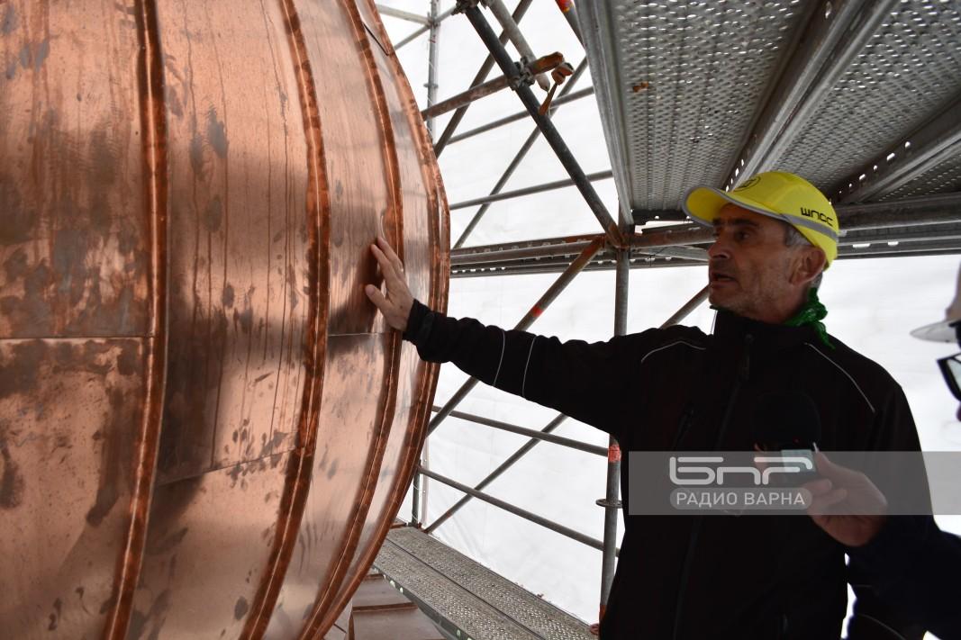 На 38 м. височина всяко парче от медната ламарина се прикрепва и заковава на ръка, пояснява Анатоли Серафимов. Разстоянието между кубето и платформата, върху която работят и стъпват работниците е между 30 см и повече от метър.