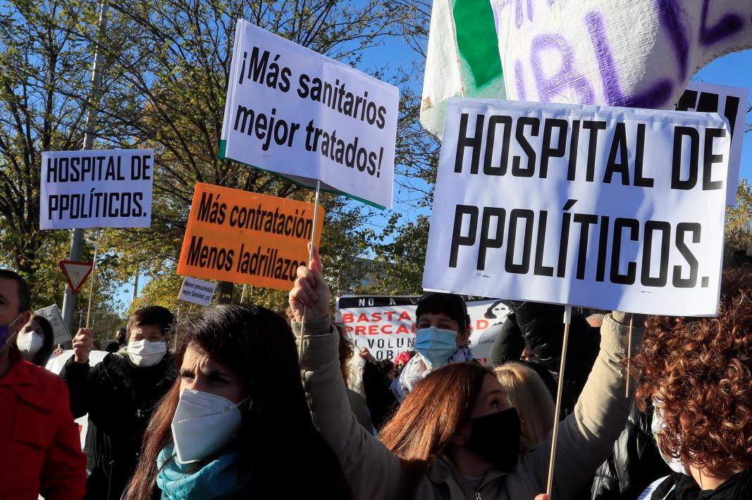 """Парамедици на протест по време на церемонията по откриването на новата болница в Мадрид. На първа линия се чете надпис  """"Болница на политиците"""" -1 декември 2020 г."""