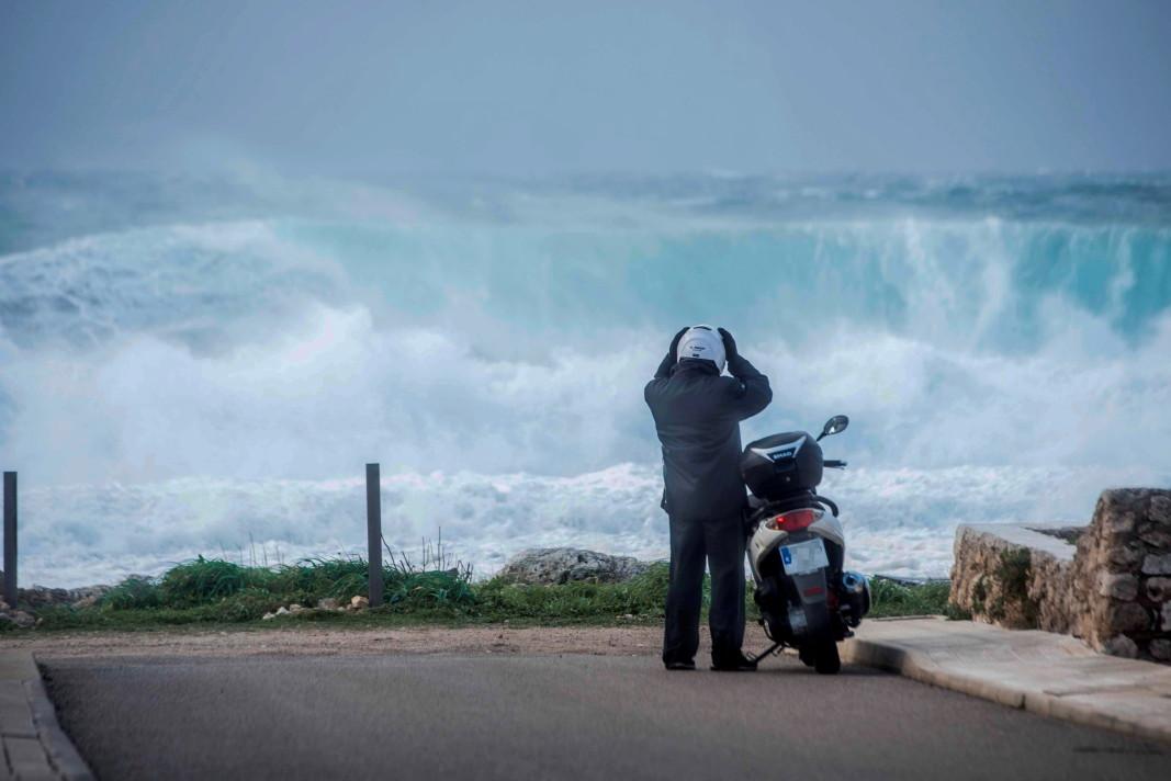 Мотоциклетист е спрял, за да наблюдава вълните, които се разбиват на плаж в Менорка, Испания, 28 декември 2020 г.