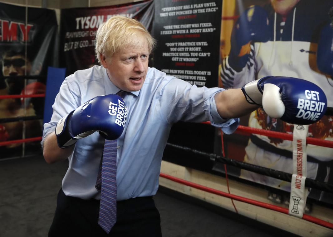 """Борис Джонсън в клуб в Манчестър с боксови ръкавици с надпис на тях """"Да изпълним Брекзит"""". Снимка БТА"""