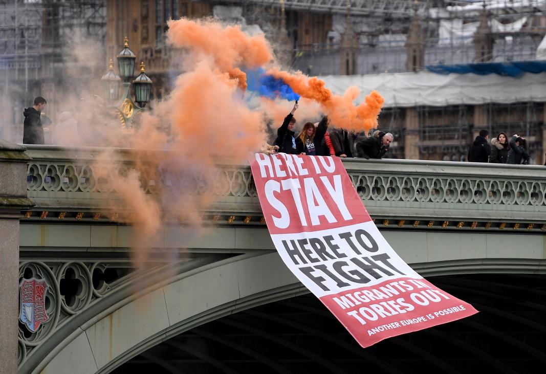 """Привърженици на оставането в ЕС развяха транспарант с надпис """"Тук ще останем, тук ще се борим. Имигрантите - вътре, торите - вън!"""". Снимка: ЕПА/БГНЕС"""