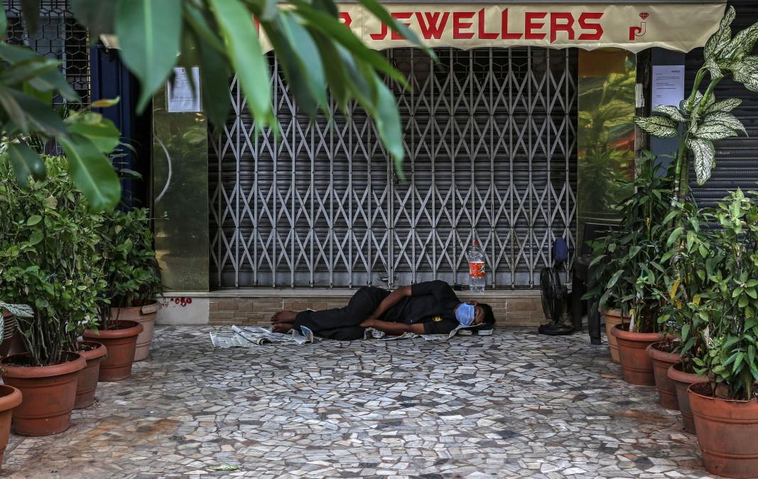 Охранител спи пред магазин в Мумбай, 3 април 2020 г.        Снимка: ЕПА/БГНЕС
