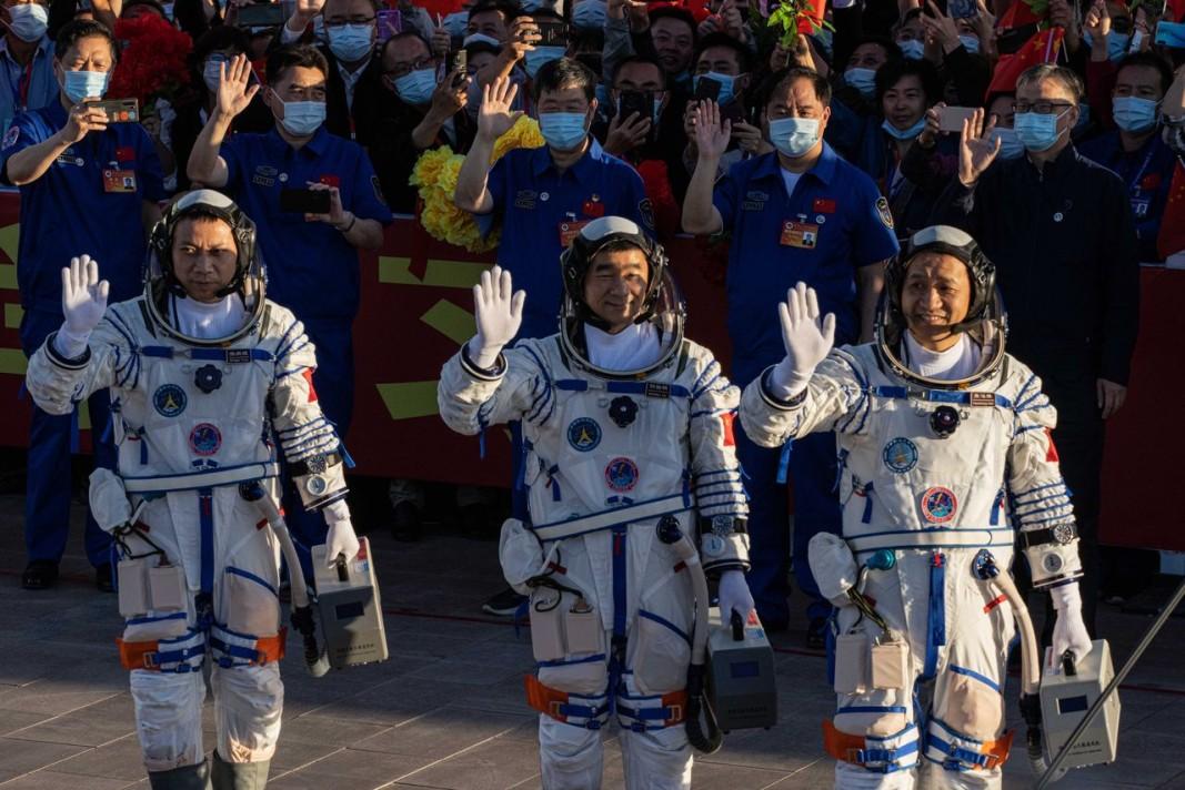 Китайските тайкунавти Тан Хонбо, Не Хайшън и Лю Бомин махат на церемонията по изпращането им. Снимка ЕПА/БГНЕС