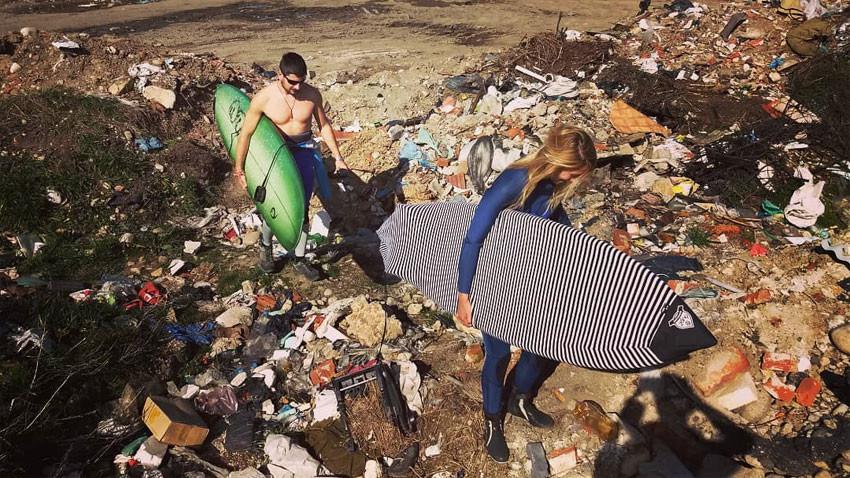Илијана Стоилова и Јоан Колев прелазе кроз гомилу отпада на обали током своје акције