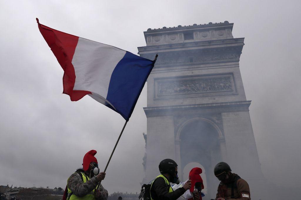 """Демонстранти от движение на """"жълтите жилетки"""" – символ срещу поскъпването на горивата, на протест в центъра на Париж."""
