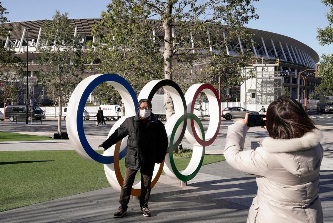Турист се снима пред олимпийските кръгове в Токио.