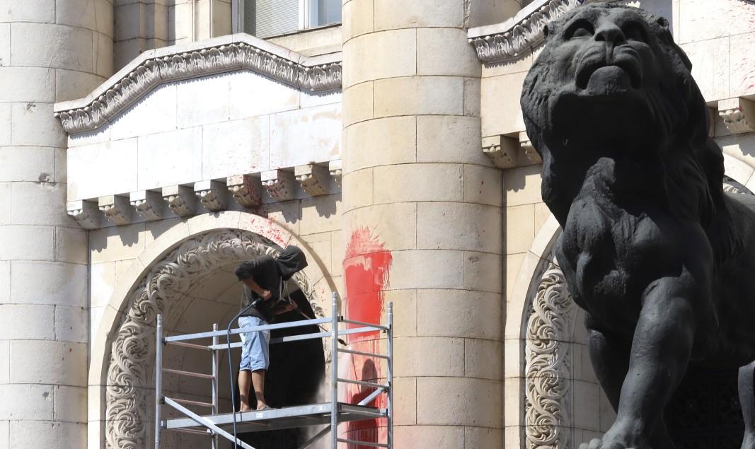 Служители на Столичен инспекторат почистват червената боя, която беше хвърлена от протестиращи, върху фасадата на Съдебната палата, 4 август 2020 г.        Снимка: БГНЕС
