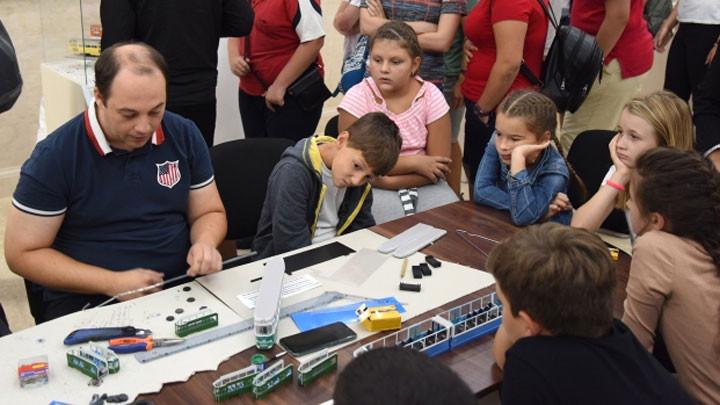 Деца и възрастни гледат как се правят макети на трамваи
