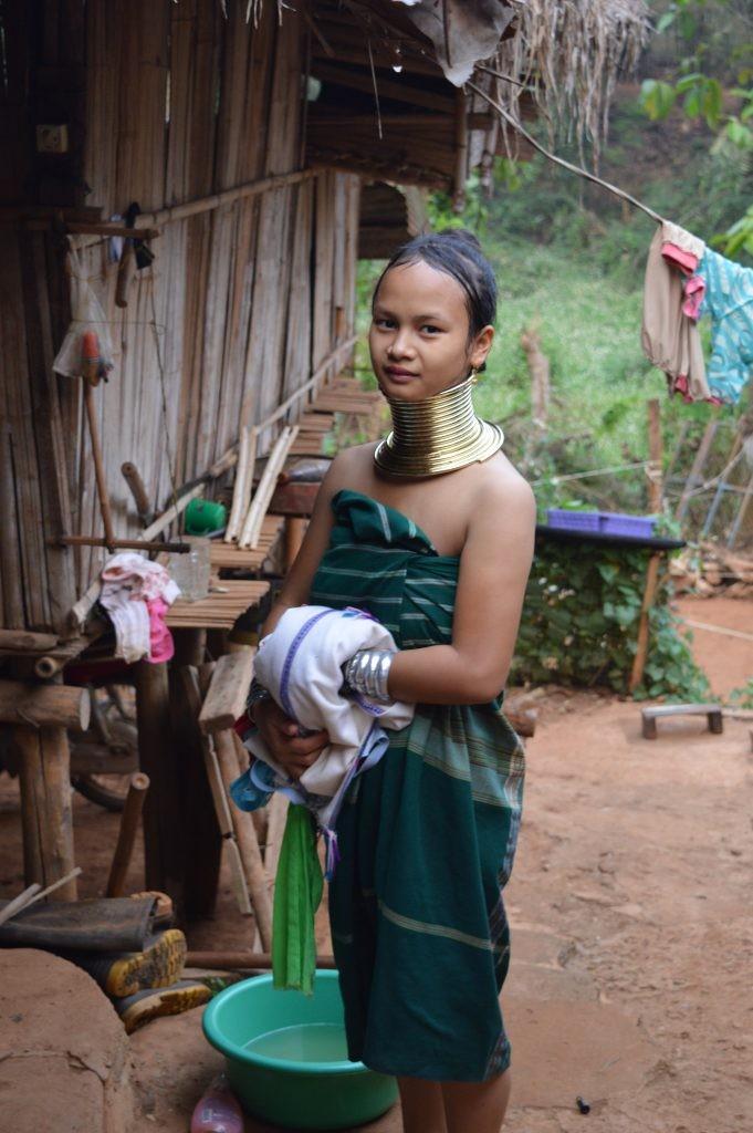 Девойка от племето Палонг излиза от банята. Ринговете на жената-жираф са истински