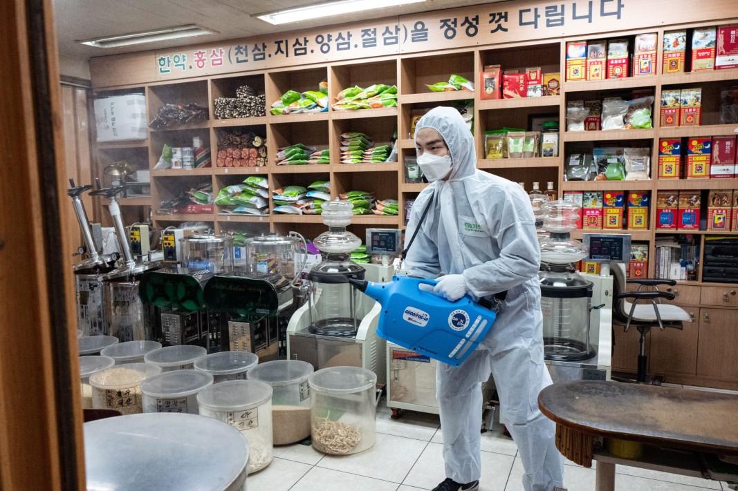 Служител на здравните власти извършва дезинфекция в магазин в Сеул
