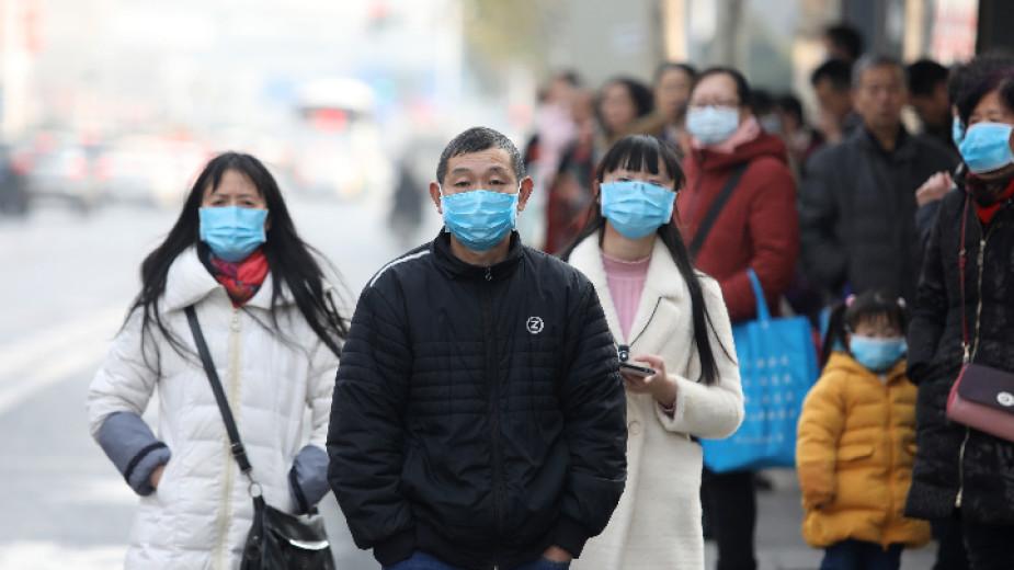 Китайци с маски чакат автобус до затворения рибен пазар Хуанан в град Ухан, провинция Хубей, смятан, че е свързан с появата на новия вирус.