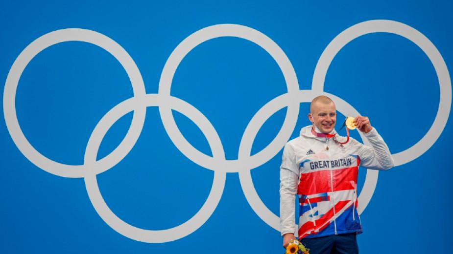 Адам Пийти показва златния си медал на награждаването.