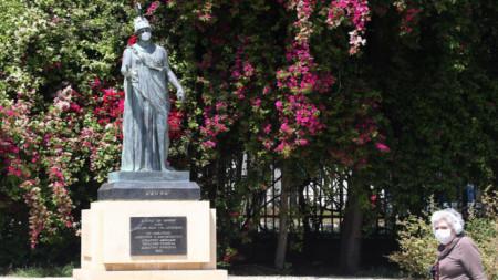 Nikosia, 22. April 2020, eine ältere Frau geht an der Statue der Göttin Athene vorbei